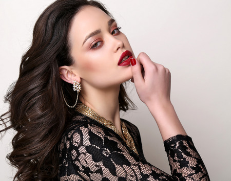 fashion studio photo of gorgeous sensual woman with dark hair and bright makeup, with luxurious accessories photo