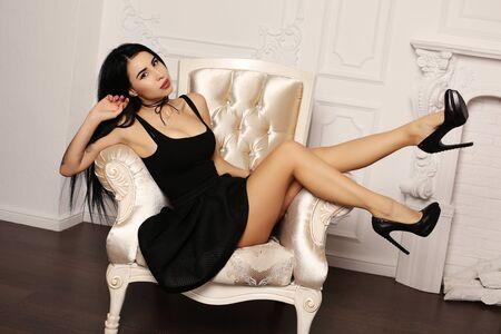 sexy model: fashion interior photo of beautiful sensual woman with dark hair in elegant dress