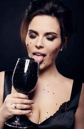 cabello negro: fashion studio photo of sexy gorgeous woman with dark hair eating black caviar