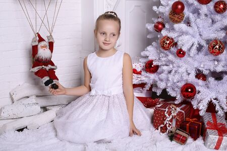child model: holiday photo. adorable cute girl with blond hair posing beside Christmas tree