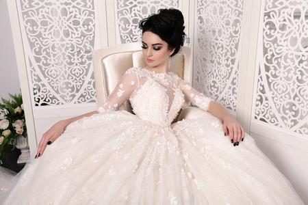 matrimonio feliz: foto de estudio de moda de la novia hermosa con el pelo oscuro en vestido de novia luxuious