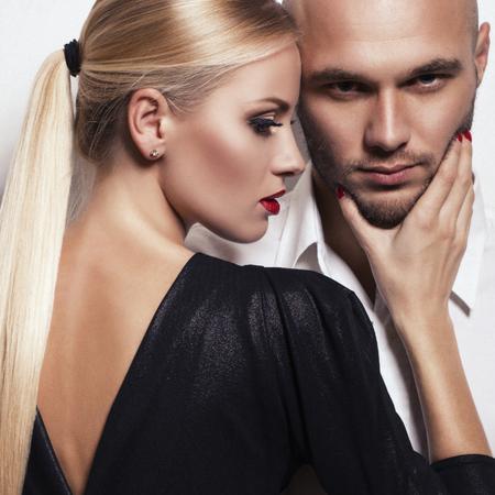 fashion studio foto van gepassioneerde paar. mooie vrouw met blond haar poseren met de knappe mens