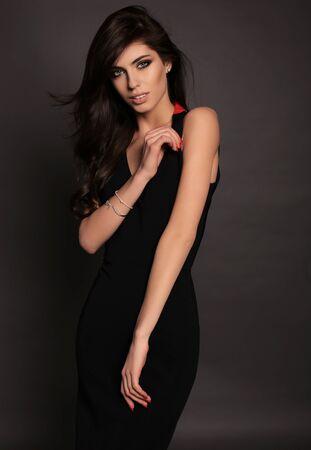 pretty hair: fashion photo of gorgeous woman with long dark hair posing in studio in elegant black dress