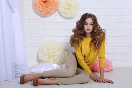 fashion interior photo of beautiful young girl with dark curly hair and glowing skin