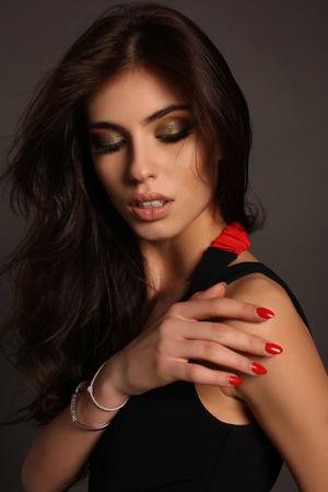 black hair: fashion photo of gorgeous woman with long dark hair posing in studio in elegant black dress