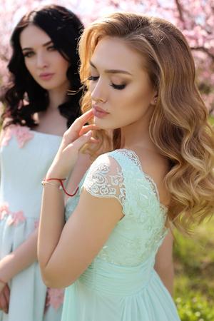 mujeres elegantes: foto al aire libre de la moda de las mujeres jóvenes hermosas en vestidos elegantes que presentan en jardín con árboles de durazno en flor