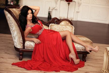 Foto di moda interni di splendida giovane donna con capelli scuri in abito lussuoso rosso in posa in studio con bouquet di fiori