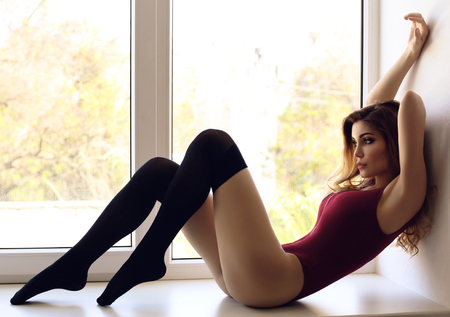 fashion interior photo of gorgeous young woman with dark hair in black lingerie posing at bedroom Archivio Fotografico