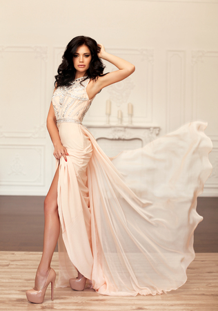 beige: fashion interior photo of gorgeous young woman with dark hair in luxurious beige dress posing at bedroom