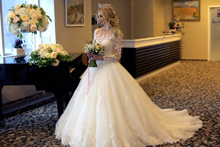fashion interior photo of gorgeous bride with blond hair in luxurious wedding dress posing in decorated room