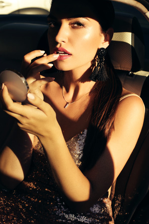 chic woman: fashion outdoor photo of gorgeous sensual woman with dark hair posing in luxurious car