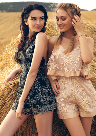 fashion outdoor photo of gorgeous girls in casual clothes posing on the hay Stock Photo