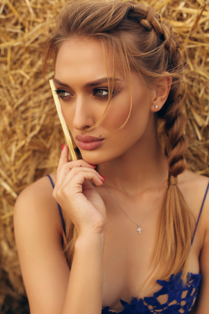 fashion outdoor photo of gorgeous girl with blond hair in elegant dress posing on the hay Stock Photo