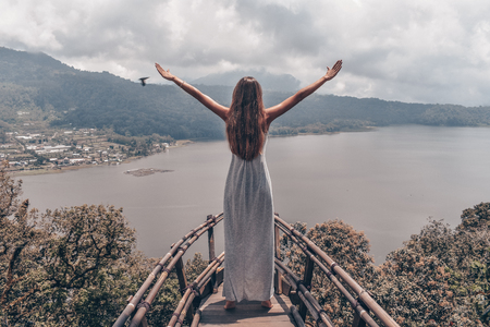 series traveling girl in Asia, beautiful girl with long dark hair in elegant grey dress posing in beautiful nature place in Bali