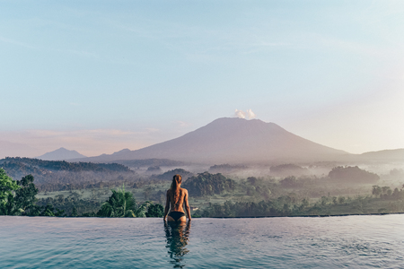 series traveling girl in Asia. beautiful girl with long dark hair in swimming suit in beautiful nature place in Bali, posing near swimming pool with volcano Agung view