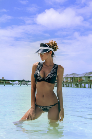 fashion photo of beautiful woman in luxurious swimming suit relaxing on Maldive islands