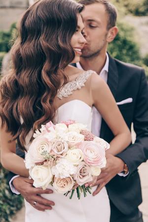 Liebesgeschichte, Hochzeitsfoto des schönen Paares. wunderschöne Frau mit dunklem Haar im luxuriösen Hochzeitskleid und ihrem hübschen Ehemann, der im Frühlingspark aufwirft