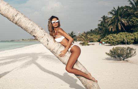 fashion outdoor photo of beautiful sexy woman with blond hair in luxurious bikini relaxing near palm tree on Maldive island