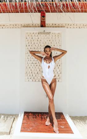 fashion photo of beautiful sexy woman with blond hair in luxurious bikini relaxing on Maldive island,taking outdoor beach shower  Stock Photo