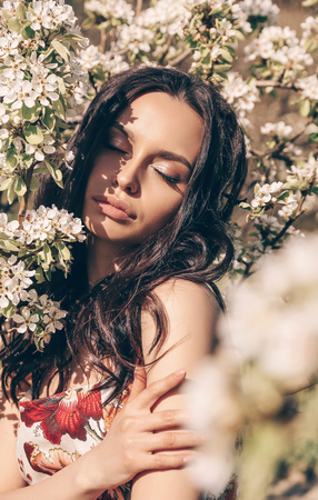 fashion outdoor photo of beautiful woman with dark hair in elegant clothes posing in spring field with reeds