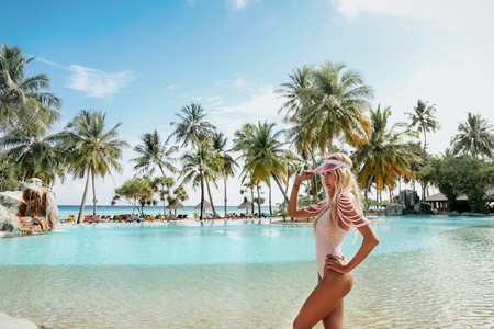 fashion outdoor photo of beautiful sexy woman with blond hair in elegant beach clothes relaxing in Maldive island