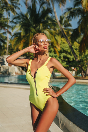 fashion outdoor photo of sexy woman with blond hair in elegant swimming suit relaxing near swimming pool in Maldive island Stock Photo