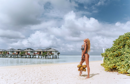 fashion outdoor photo of beautiful sexy woman with blond hair in elegant beach clothes relaxing in Maldive island, holding bunch of coconuts