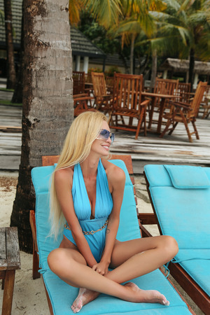 fashion outdoor photo of beautiful sexy woman with blond hair in elegant swimming suit relaxing on chaise longue on the Maldive's beach Stock Photo