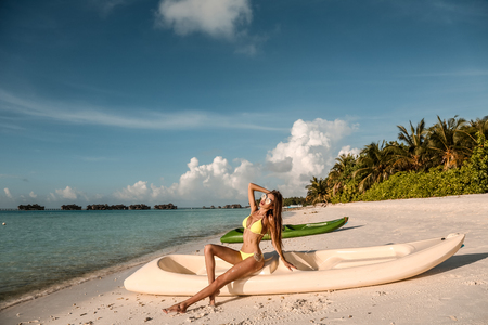 fashion photo of beautiful sexy girl with dark hair in elegant beach clothes, relaxing on Maldive island beach