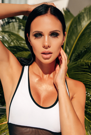fashion outdoor photo of beautiful sexy woman with dark hair in elegant swimming suit relaxing in luxurious villa