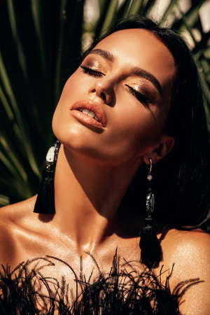 fashion outdoor photo of sexy beautiful woman with dark hair in luxurious black cocktail dress posing in villa Banco de Imagens