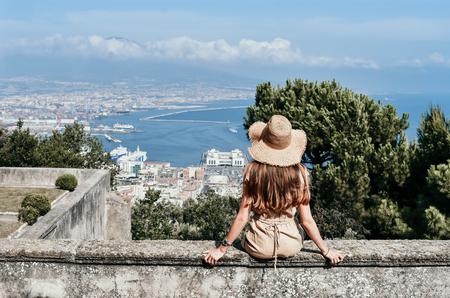 Photo en plein air de mode de belle femme aux longs cheveux noirs en robe élégante et chapeau de paille voyageant en Italie, assis dans le vieux château avec vue sur le Vésuve et Naples