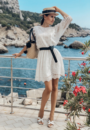 fashion outdoor photo of beautiful sensual girl with dark hair in elegant dress and accessories posing near the sea Stock Photo