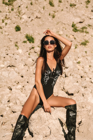 Fashion outdoor photo of beautiful sensual girl with dark hair in elegant swimming suit and accessories posing in desert
