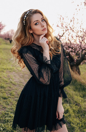 fashion outdoor photo of beautiful sensual girl with blond hair in elegant black dress and headband posing in blooming peach garden Stockfoto