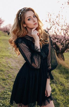 Mode-Outdoor-Foto eines schönen sinnlichen Mädchens mit blonden Haaren in elegantem schwarzem Kleid und Stirnband, das im blühenden Pfirsichgarten posiert