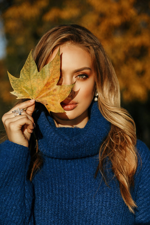 fashion outdoor photo of beautiful woman with blond hair in elegant outfit posing in autumn park Imagens