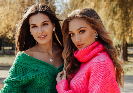 fashion outdoor photo of beautiful women in elegant bright cardigans posing in autumn park Imagens
