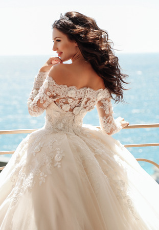 fashion outdoor photo of beautiful bride with dark hair in luxurious wedding dress posing in balcony with sea view
