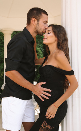 fashion outdoor photo of beautiful tender couple. gorgeous pregnant woman with dark hair in elegant dress posing with her handsome husband in elegant villa