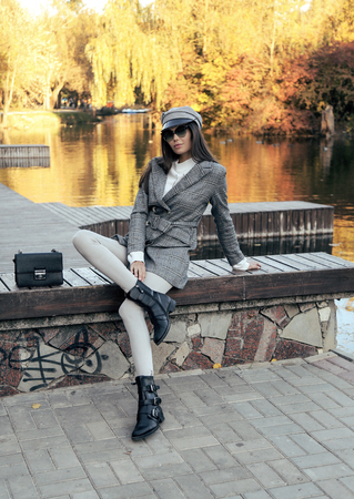 fashion outdoor photo of beautiful sexy woman with dark hair in elegant clothes and accessories posing in autumn park Imagens