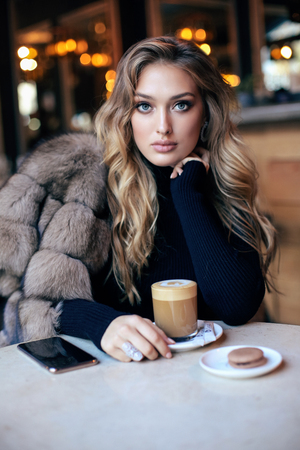fashion interior photo of beautiful woman with blond curly hair in elegant fur coat, dress and accessories, sitting in cafe, drinking a coffee with dessert Stock Photo
