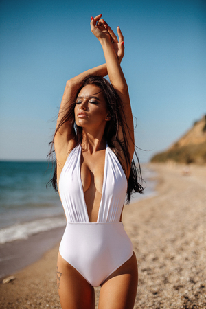 fashion outdoor photo of beautiful girl with dark hair in elegant swimming suit relaxing on the summer beach Imagens