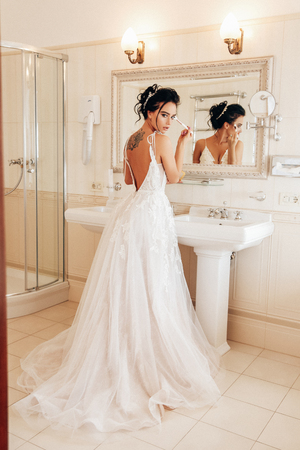 fashion photo of beautiful woman bride with long dark hair in luxurious wedding dress and accessories posing in elegant interior