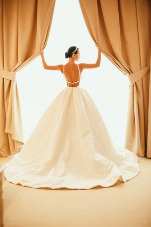 fashion photo of beautiful sensual bride with dark hair in luxurious wedding dress and accessories posing in elegant interior of hotel