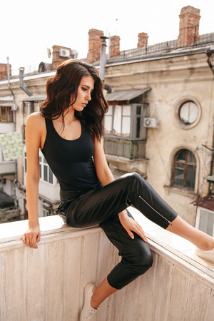fashion photo of beautiful sexy woman with dark hair in elegant clothes posing in balcony with old city view on background