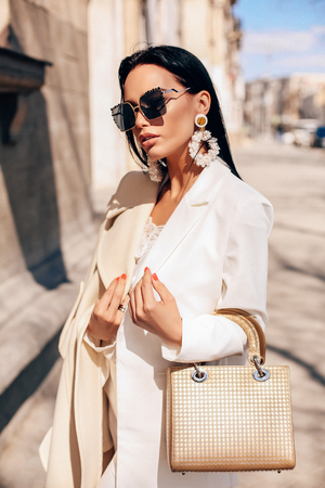 fashion outdoor photo of beautiful woman with dark hair in elegant clothes with accessories, walking by the spring street 스톡 콘텐츠