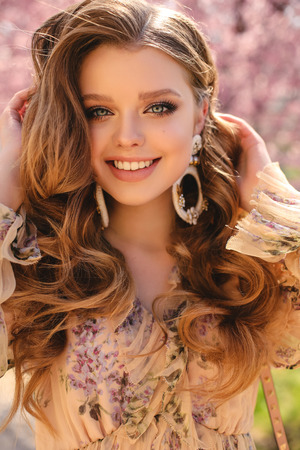 Mode-Outdoor-Foto eines schönen jungen Mädchens mit natürlicher Haarfarbe in eleganter Kleidung, das zwischen blühenden Pfirsichbäumen im Frühlingsgarten posiert