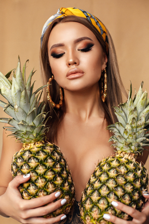fashion photo of beautiful woman with dark hair and evening makeup, with silk headband and earrings, holding two pineapples on her