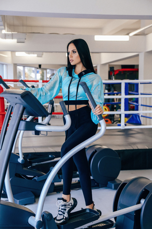 fashion photo of beautiful sexy woman with dark hair in sportive clothes  training in gym